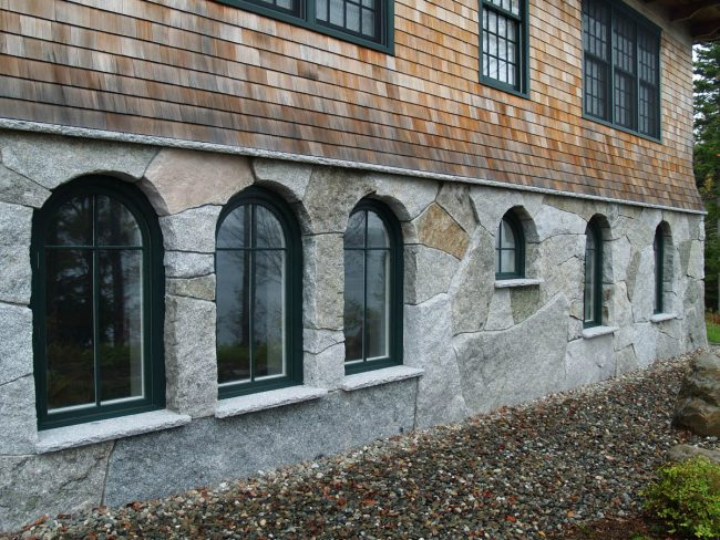 Weathered, split face granite stone on houses, featuring drill holes and Freshwater Pearl granite window sills