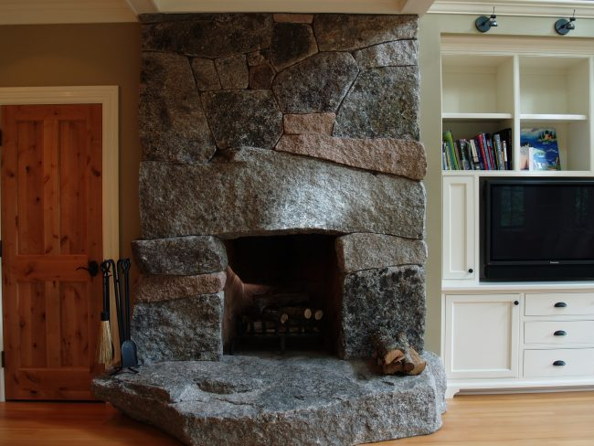 Raised hearth fireplace with weathered, mixed granite