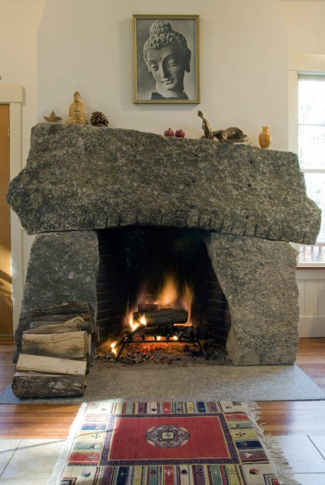 Weathered, three stone fireplace, featuring drill holes