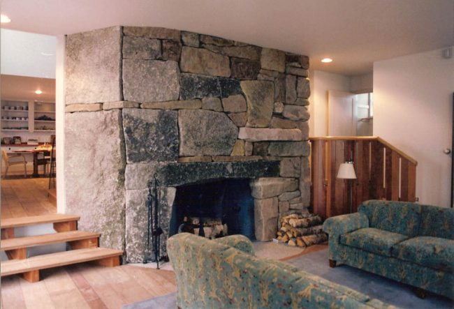 Weathered, split face granite fireplace, with a curved hearth stone