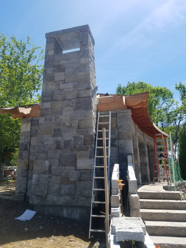 Chimney installation featuring weathered, mixed granite and a granite chimney cap