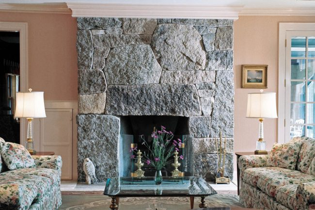 Natural, split face granite fireplace, with weathering and drill holes