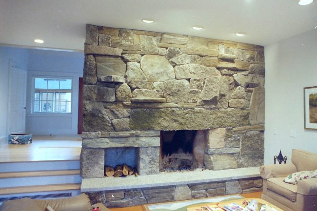 Weathered granite fireplace, with a wood box and raised hearth stone
