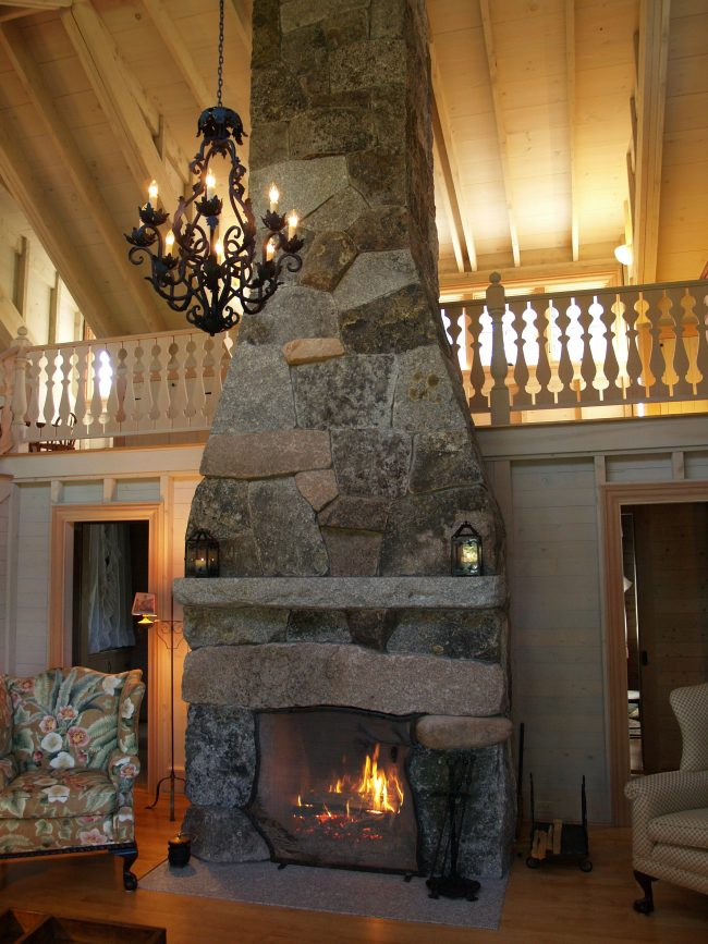 Weathered, mixed granite fireplace with a flush hearth and full height