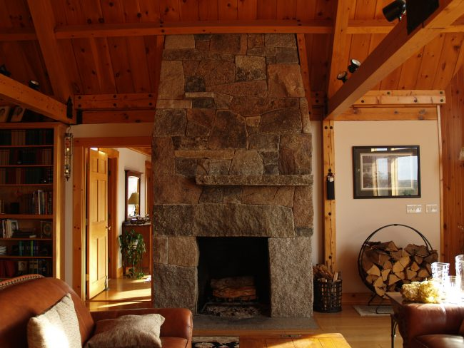 Weathered, mixed granite fireplace with a flush hearth
