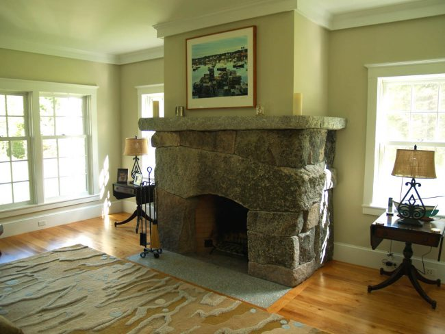 Weathered, multi-color fireplace, with a flush hearth stone