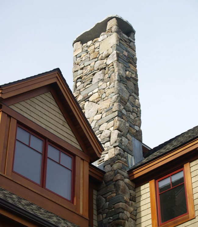 Weathered field stone chimney with a granite chimney cap