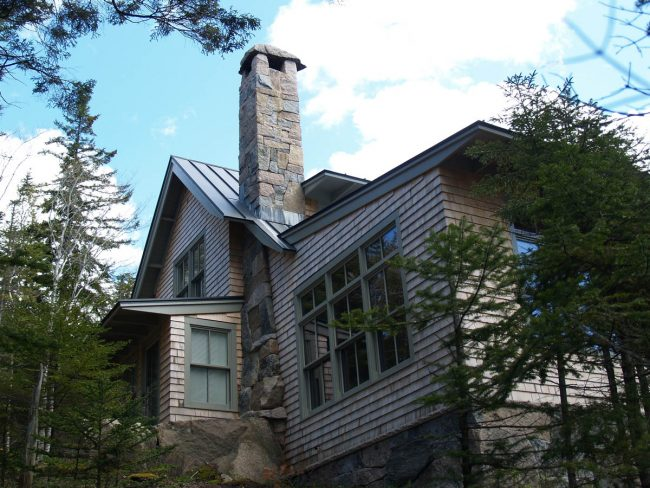 Multi-color granite chimney, with a granite chimney cap and a boulder base