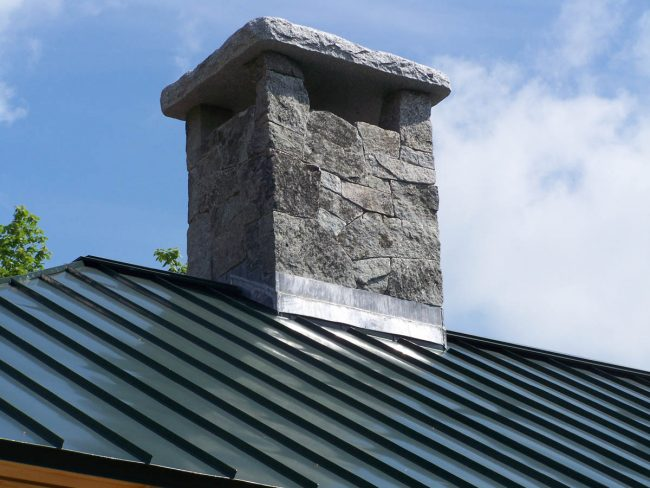 Weathered Freshwater Pearl granite chimney, with a granite chimney cap