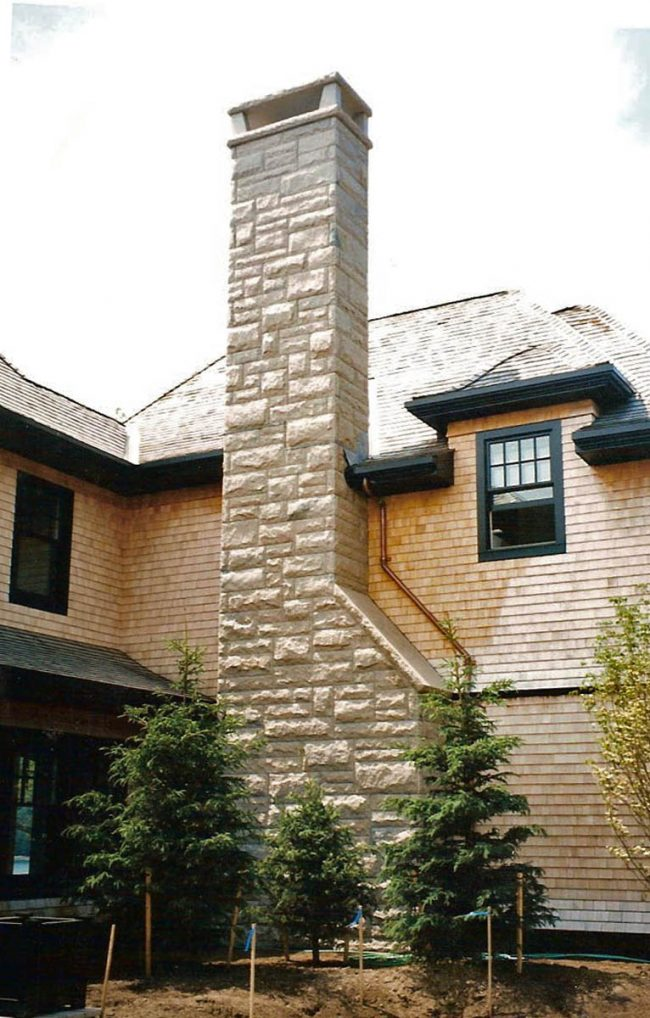 Rock face granite block chimney, with a granite chimney cap
