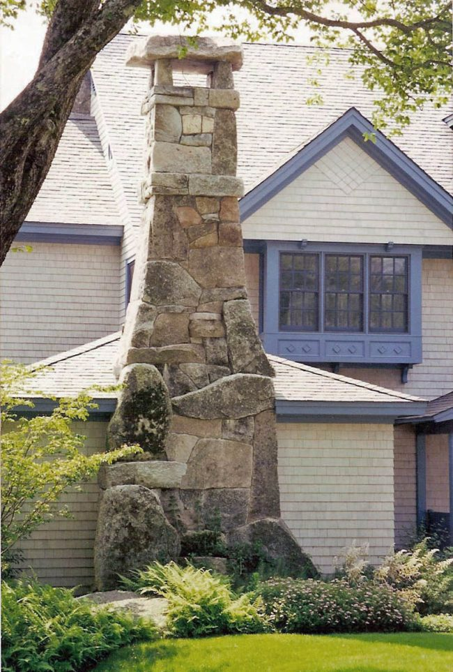 Weathered, split face granite chimney, with an irregular chimney cap - At time of installation