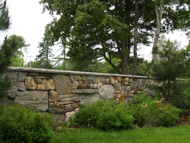 Weathered granite and field stone wall with rock face granite coping