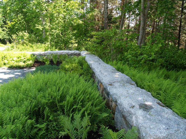 Weathered granite and field stone wall with rock face Freshwater Pearl coping