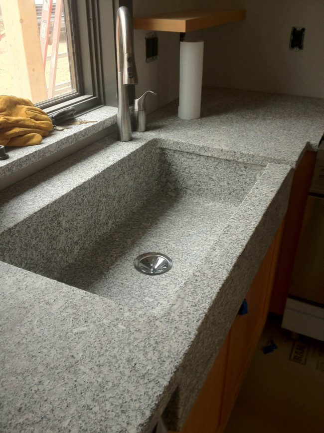 Freshwater Pearl granite counter top with an eased edge profile, and a custom Freshwater Pearl granite farmhouse sink