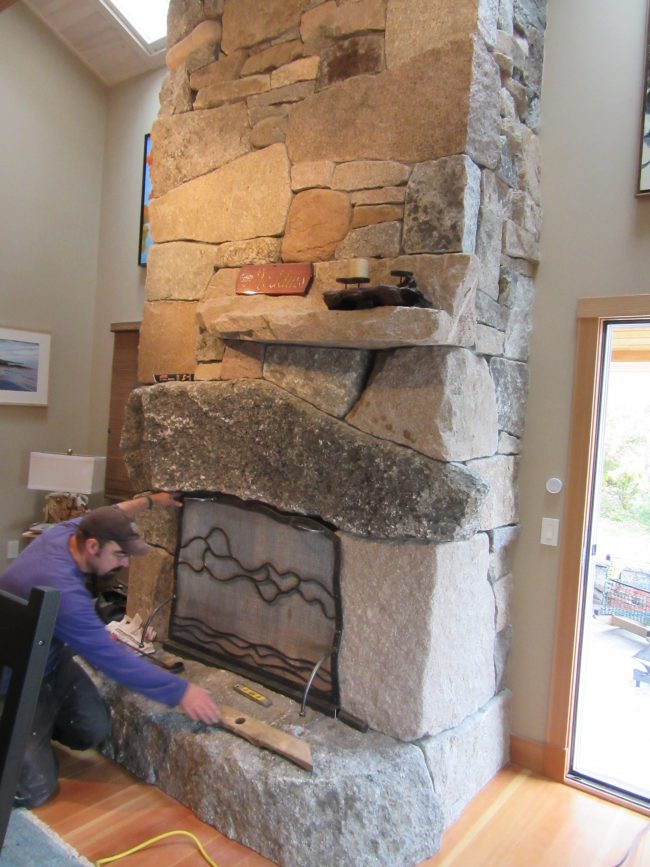 Full height, mixed granite fireplace with partial-width mantel and raised hearth
