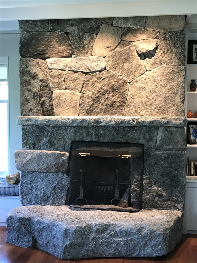 Weathered granite fireplace with mantel and irregular-shaped, raised hearth