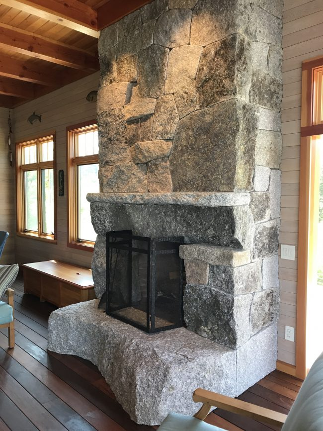 Weathered granite fireplace with a mantel and irregularly-shaped, raised hearth