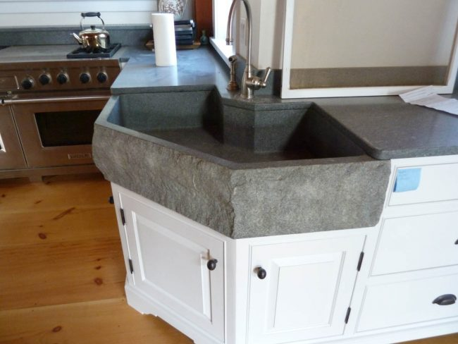 Honed Morning Mist granite counter top with an eased edge profile, with a custom farmhouse sink with a split face exterior