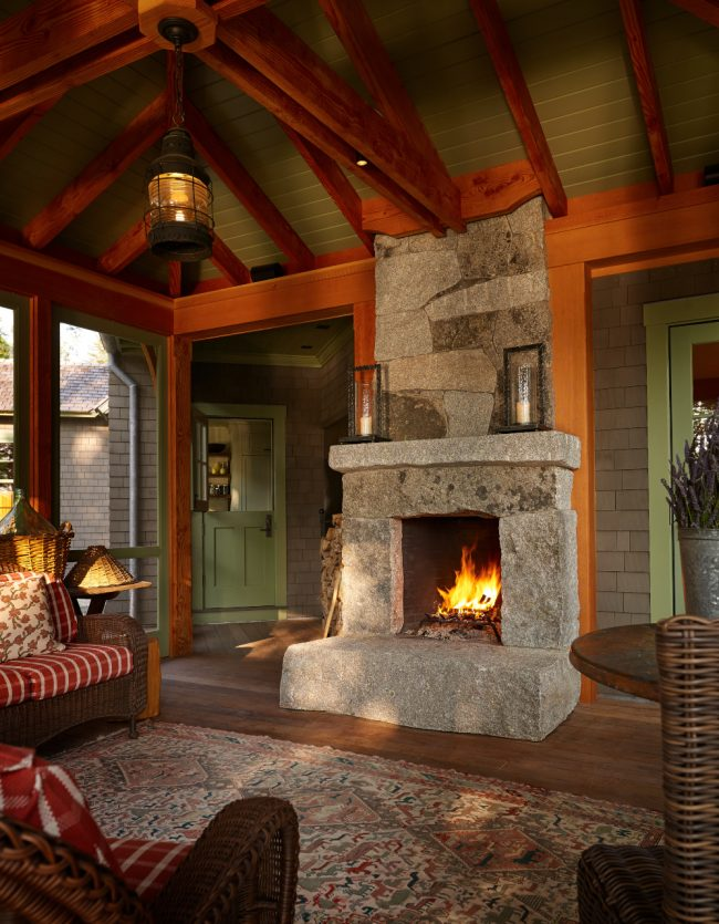 Screened-porch fireplace featuring weathered granite and drill holes, with a raised hearth