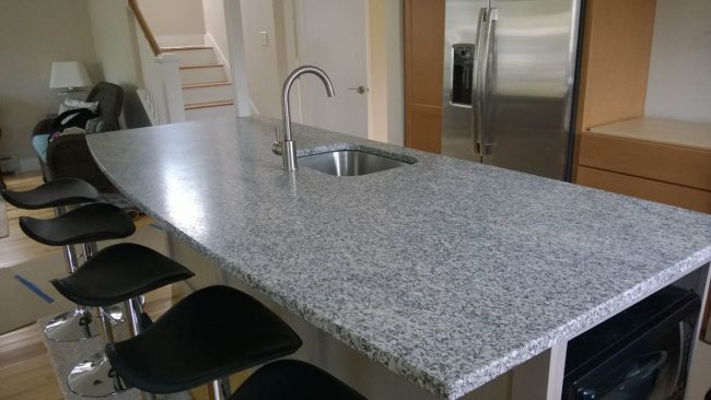 Kitchen island featuring Freshwater Pearl granite with an eased edge profile