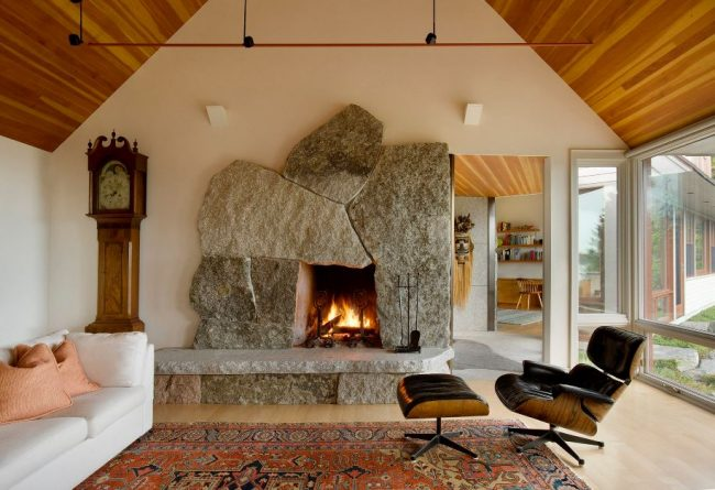 Irregular-shaped, weathered granite fireplace with a raised hearth