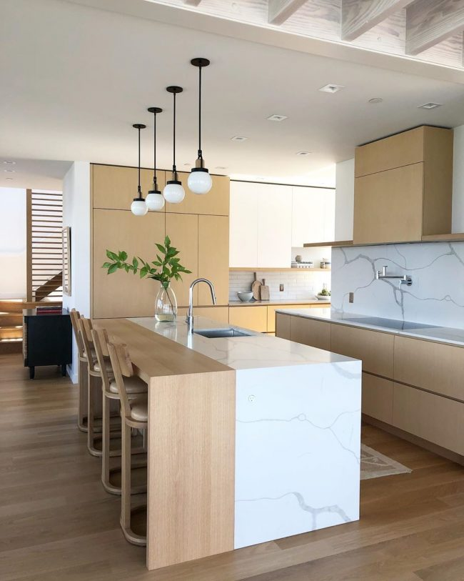 Kitchen countertops with a waterfall island and full height backsplash using a quartz marble