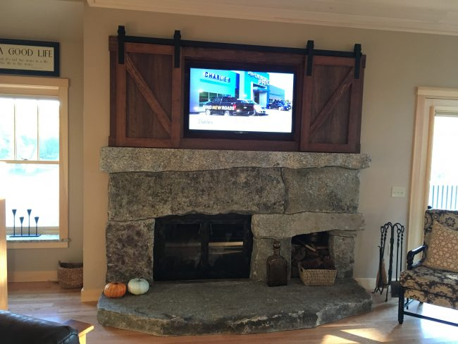 Weathered Freshwater Pearl local maine granite fireplace with built-in wood storage.
