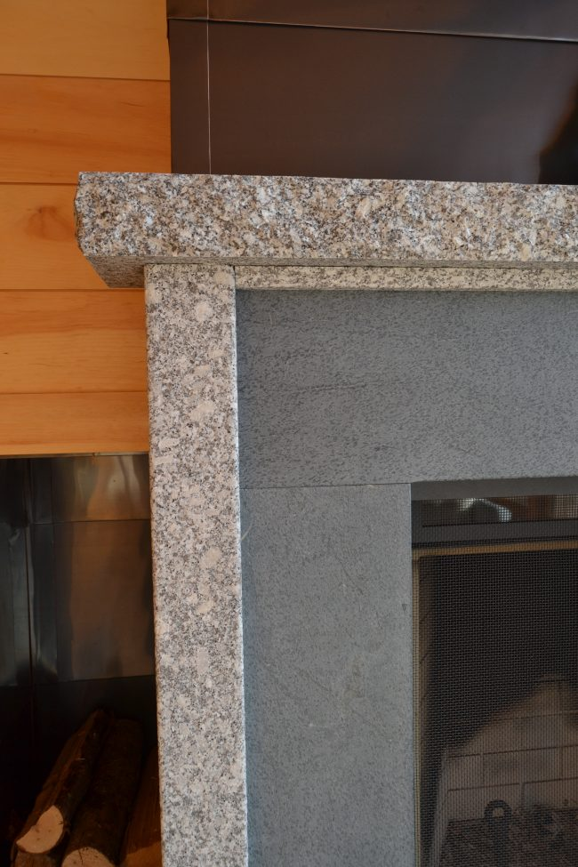 Detailed view of Freshwater Pearl granite and gray soapstone fireplace.