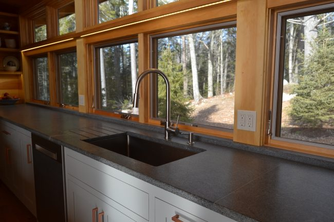 Honed Morning Mist granite countertop and backsplash, with a grooved drain board.
